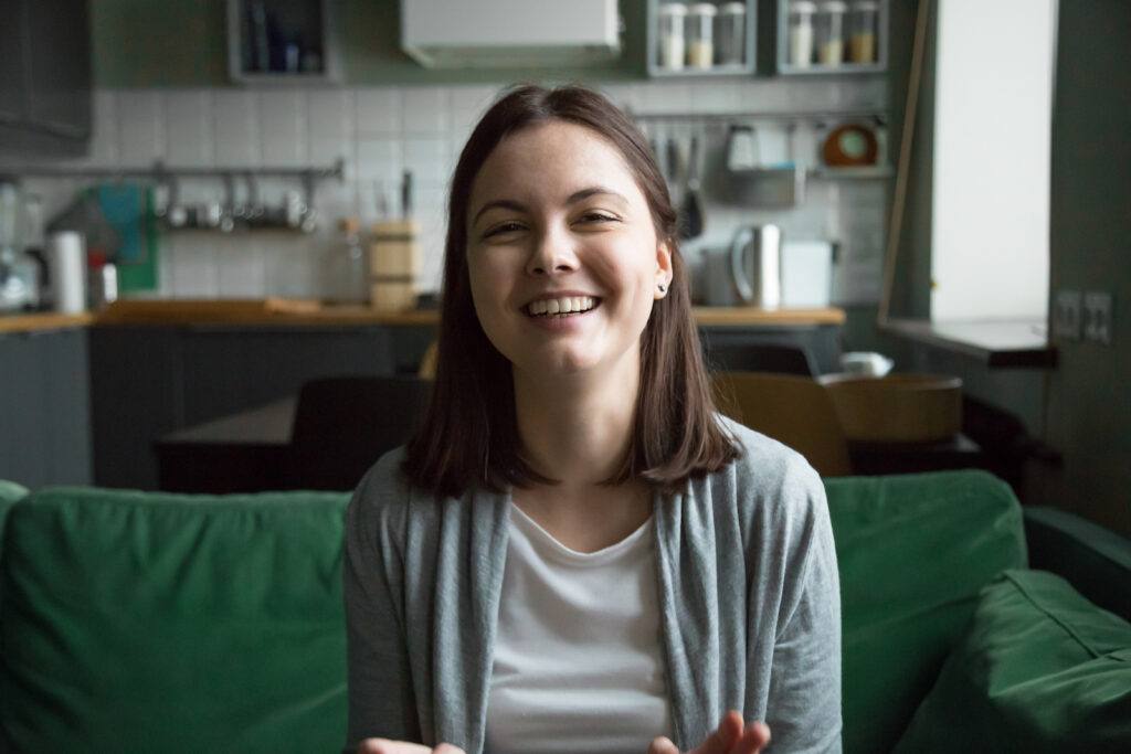 Smiling young woman answering babysitter or nanny job interview questions