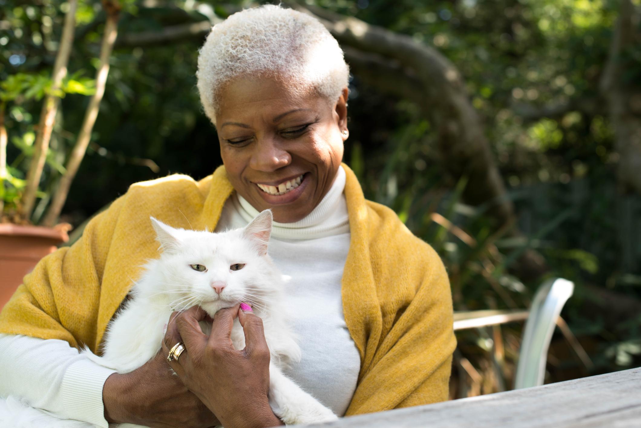 senior woman cuddling emotional support animal cat