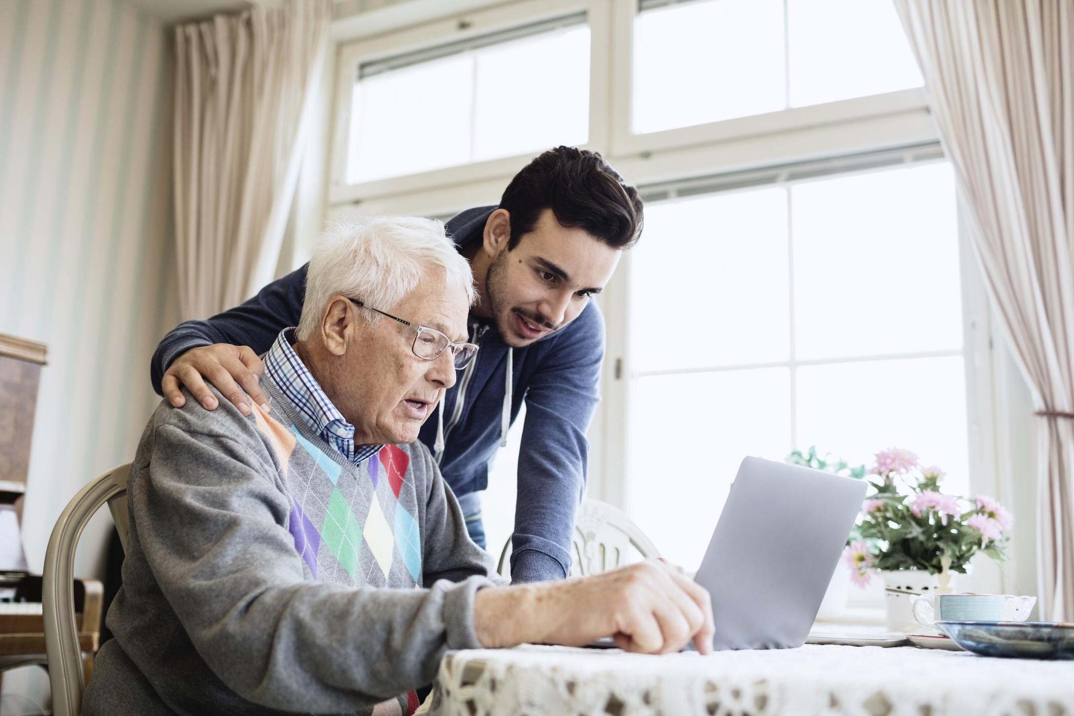 Companion caregiver and senior man using laptop