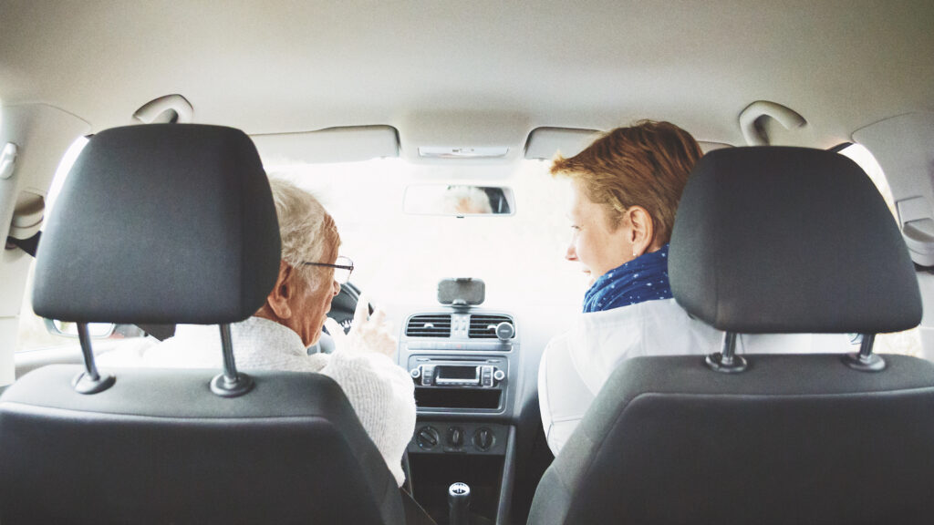 Senior father and daughter chatting while driving