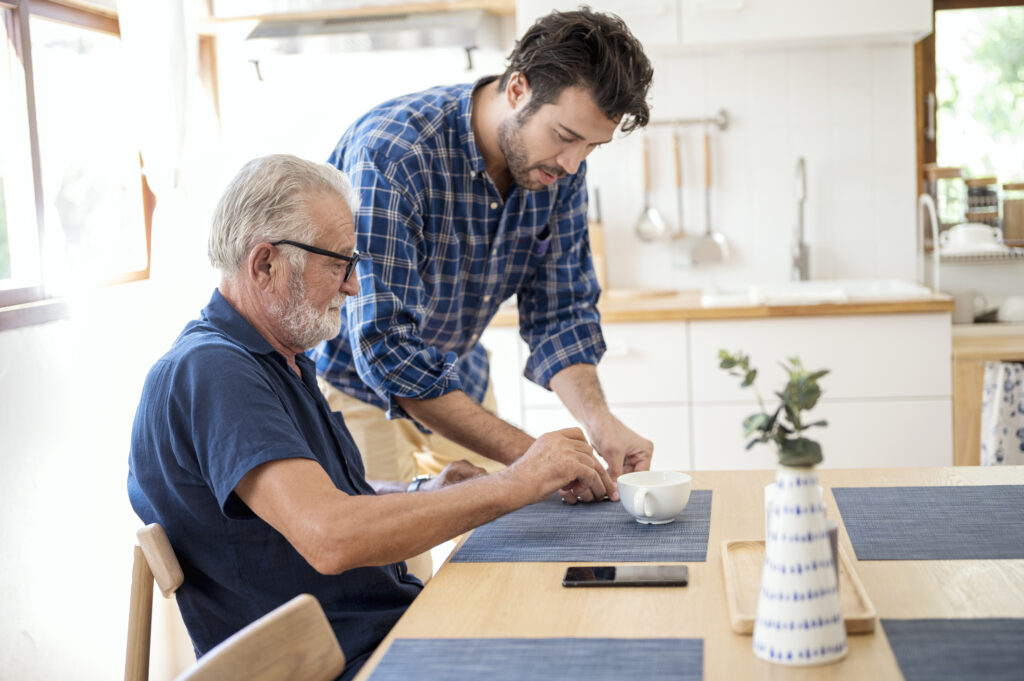 Son helping father who has dementia