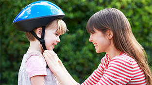 woman buckling kids helmet