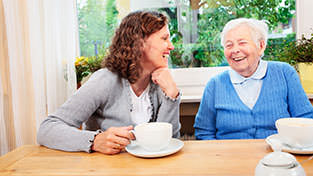 woman drinking tea with elderly woman